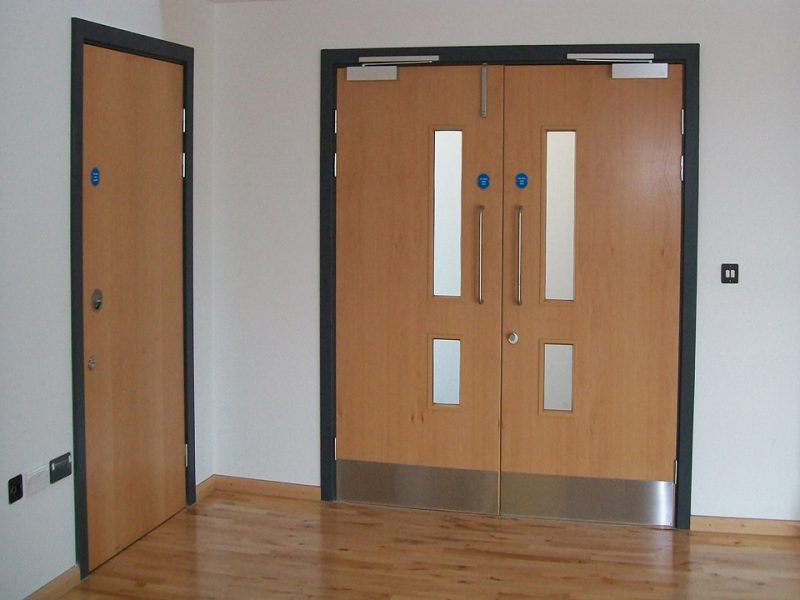 Why do all commercial buildings require fire doors?